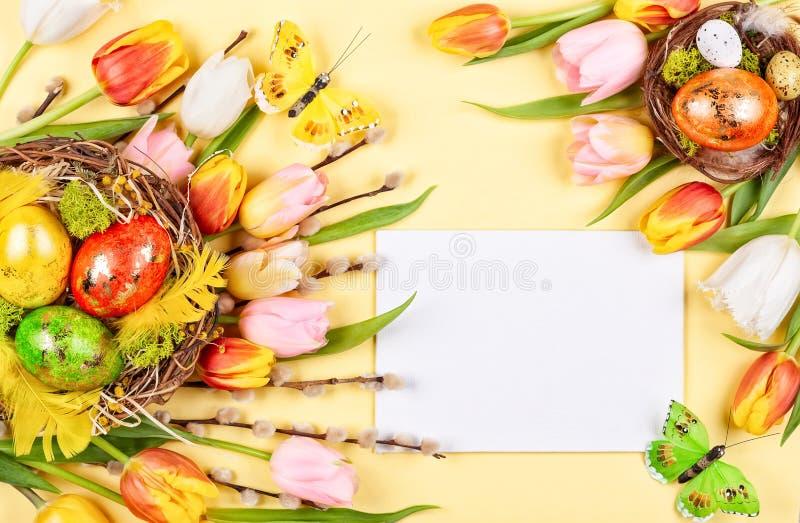 Ostern-Zusammensetzung mit Ostereiern in den Nest- und Frühlingsblumen stockbild