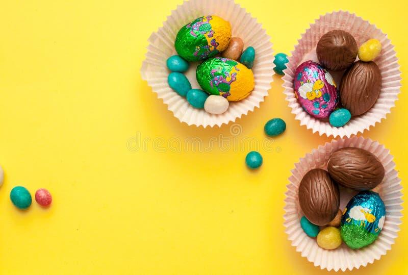 Ostern-Zusammensetzung mit Schokoladeneiern, Raum für Text Köstliche Festlichkeiten und Text auf Hintergrund stockfotos