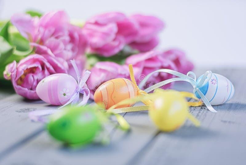 Ostern-Zusammensetzung von rosa Rosen und von farbigen Ostereiern lizenzfreies stockfoto