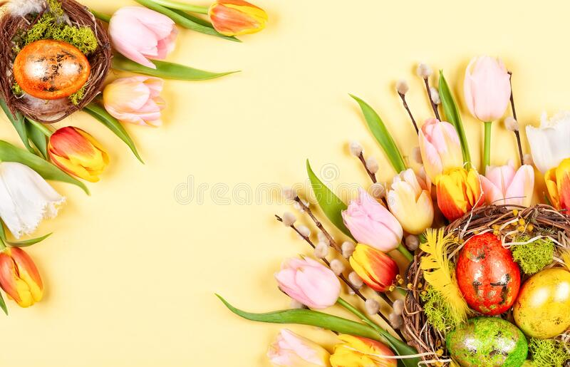 Osterzusammensetzung mit Ostereiern in Nest- und Frühlingsblüten stockfotografie
