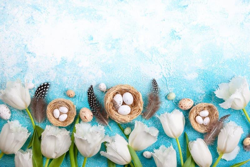 Osterzusammensetzung mit Ostereiern in Nest und weißen Tulpen stockfotos