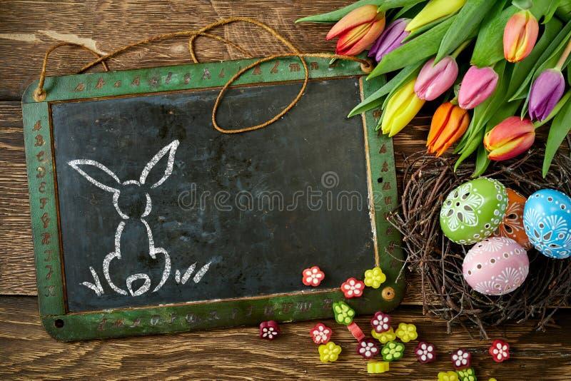 Osthäschen auf der Tafel verziert mit Tulpen lizenzfreie stockfotografie