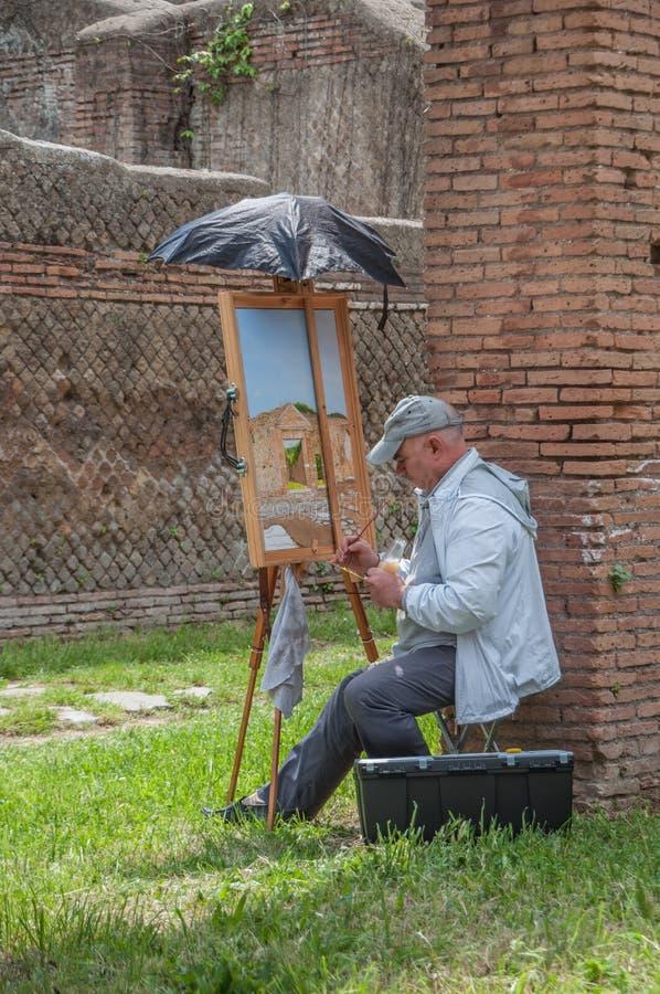 Ostia Antica, Italia - 23 de abril de 2009 - artista que pinta las ruinas del ladrillo rojo del sitio arqueológico de la ciudad d fotos de archivo libres de regalías