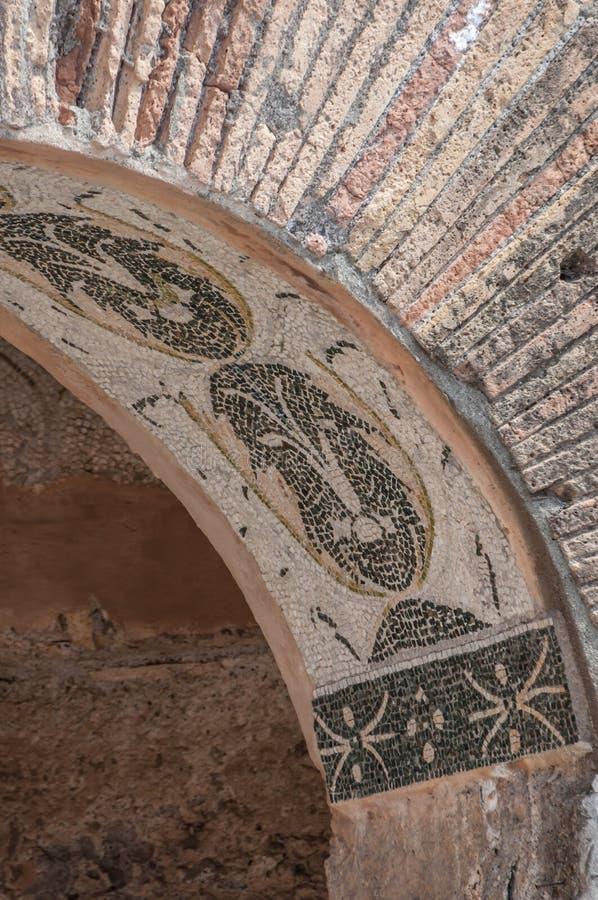 Ostia Antica, Italien - 23. April 2009 - Ruinen des roten Backsteins mit einer Mosaikfliese entwerfen in einem Torbogen in der ar lizenzfreies stockfoto