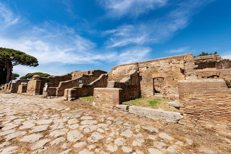 Ostia Antica Rome Italien - forntida romerska byggnader och väg royaltyfri bild