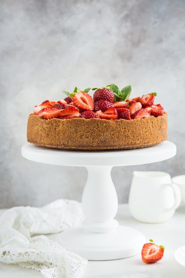 Ostkaka med den nya jordgubben på ställning för vit kaka royaltyfri foto