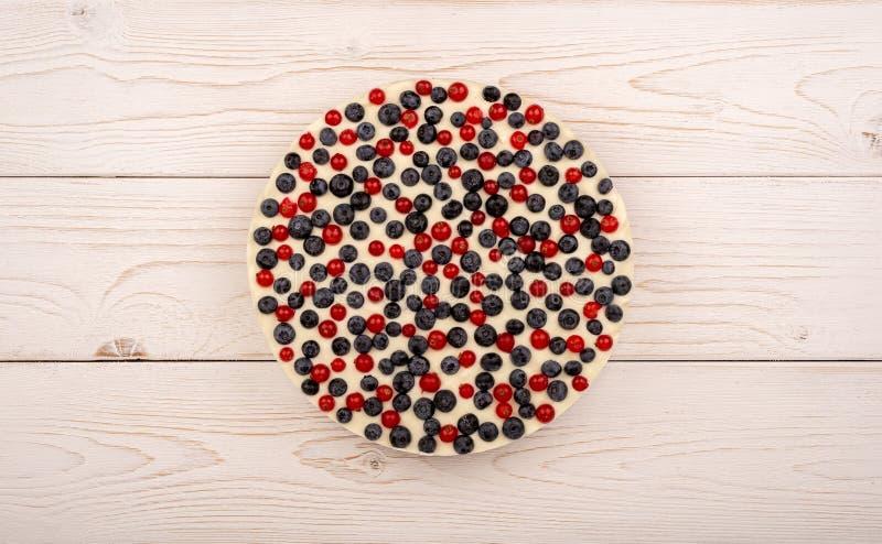 Ostkaka med röda vinbär och blåbär på träbakgrunden fotografering för bildbyråer