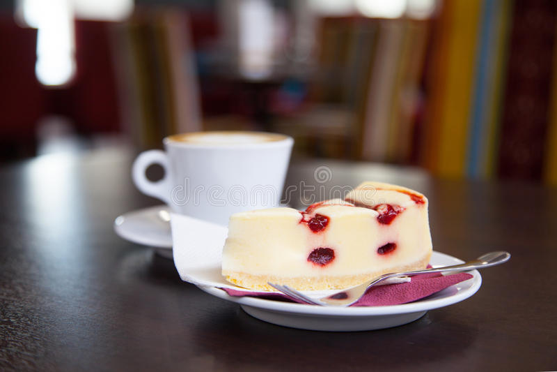 Ostkaka- och kaffekopp på en tabell i ett kafé arkivfoton
