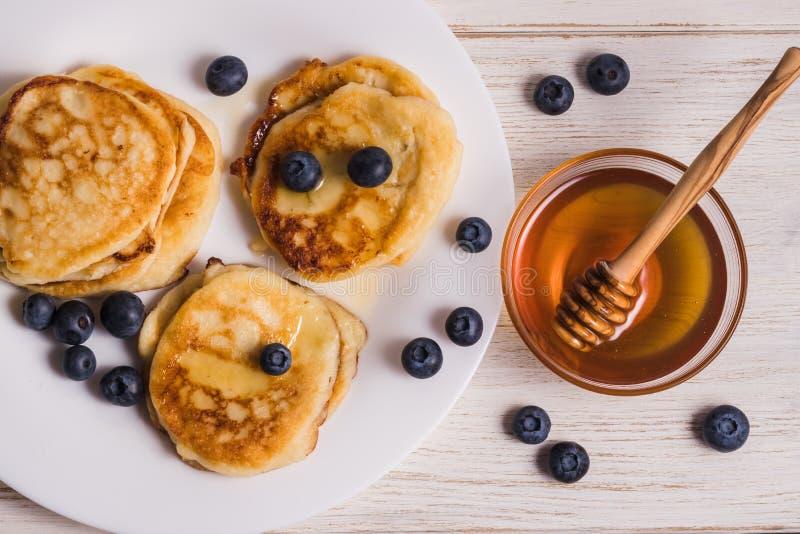 Ostkakor på en platta med blåbär, den högra plattan med honung och en träsked för honung royaltyfria foton