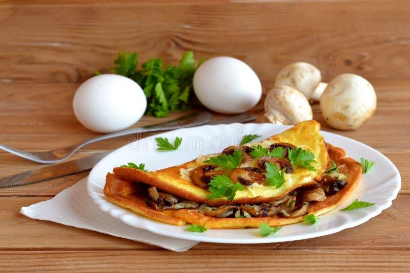Ostliknande champinjonomelett Omelett med stekt champinjoner, ost och persilja Frukostäggrecept Panna stekt omelett royaltyfri bild
