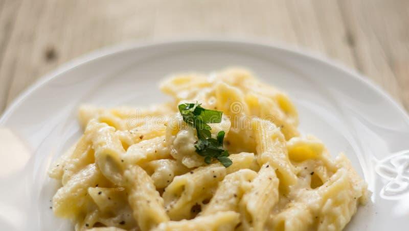Ostpasta för italienare fyra på den vita plattan på den lantliga tabellen med en gaffel på en sida fotografering för bildbyråer