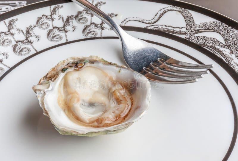 A ostra fresca e suculenta crua aberta serviu na placa cerâmica luxuosa foto de stock