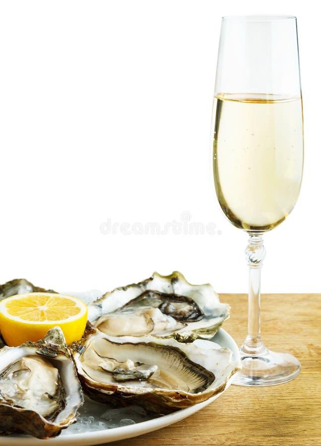 Ostras en una placa blanca con el limón y un vidrio de vino en una tabla de madera imagen de archivo