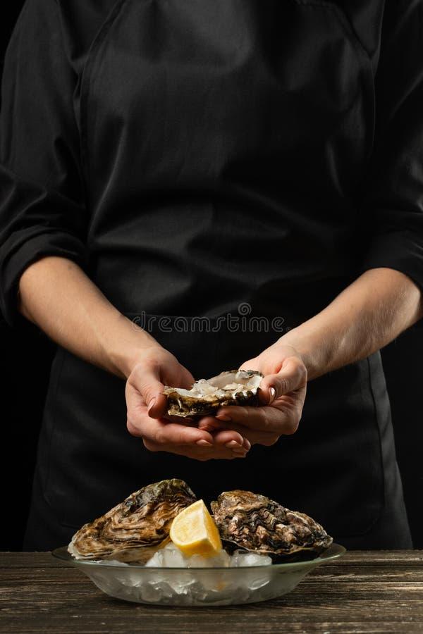 Ostras en una placa con hielo y el limón, en las manos del cocinero, en un fondo de madera Mariscos, restaurante, gusto delicioso fotografía de archivo