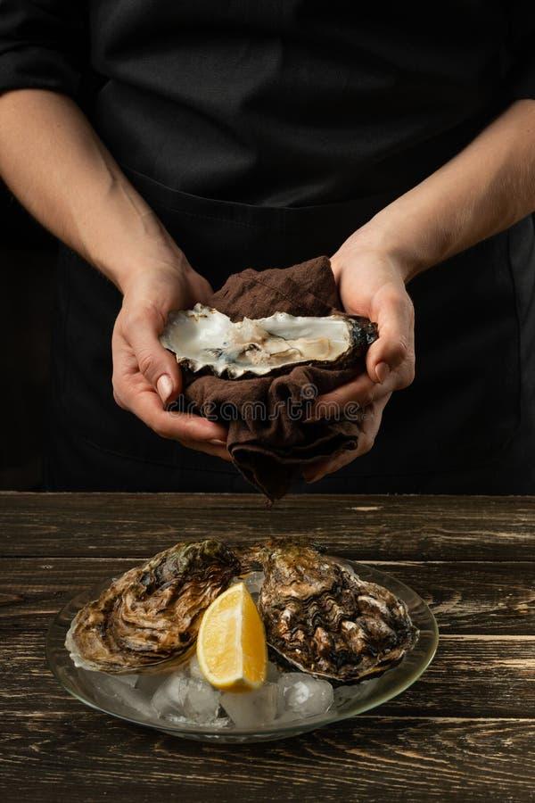 Ostras en una placa con hielo y el limón, en las manos del cocinero, en un fondo de madera Mariscos, restaurante, gusto delicioso imagen de archivo
