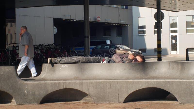 OSTRAVA, TSJECHISCHE REPUBLIEK, 28 AUGUSTUS, 2018: Authentieke emotie dakloze mens in slaap op een bank en lopende mensen royalty-vrije stock foto's