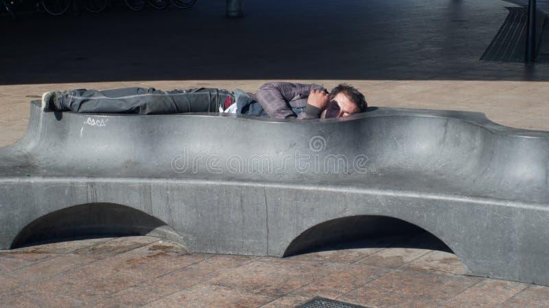 OSTRAVA, TSJECHISCHE REPUBLIEK, 28 AUGUSTUS, 2018: Authentieke emotie dakloze mens in slaap op een bank en een stoep, het leven o royalty-vrije stock foto