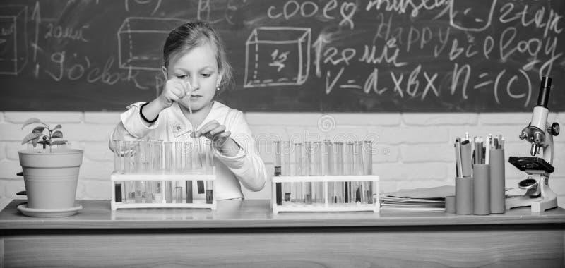 Ostre zabawy uczennicą z probówkami i barwnymi cieczami Eksperyment chemiczny w szkole Edukacja szkolna Interesujące fotografia royalty free