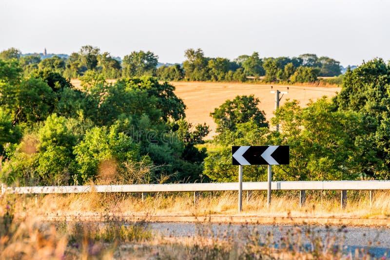 Ostrego zwrota kierunkowy znak na Brytyjskiej drodze nad wsi wiejskim lanscape obrazy royalty free