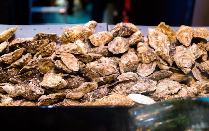Ostriche sul contatore in scatole di legno sul mercato Ostriche da vendere al mercato dei frutti di mare Stalla del mercato ittic fotografia stock