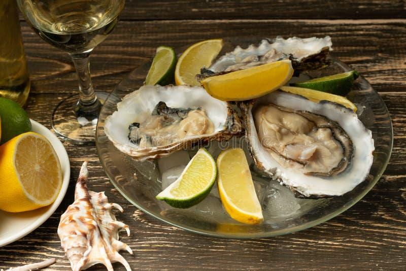 Ostriche in un piatto con ghiaccio ed il limone, con un vetro di vino secco bianco su un fondo di legno Frutti di mare, ristorant fotografie stock libere da diritti