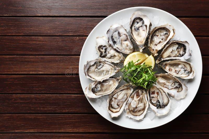 Ostriche in un piatto su un fondo di legno marrone, frutti di mare immagine stock