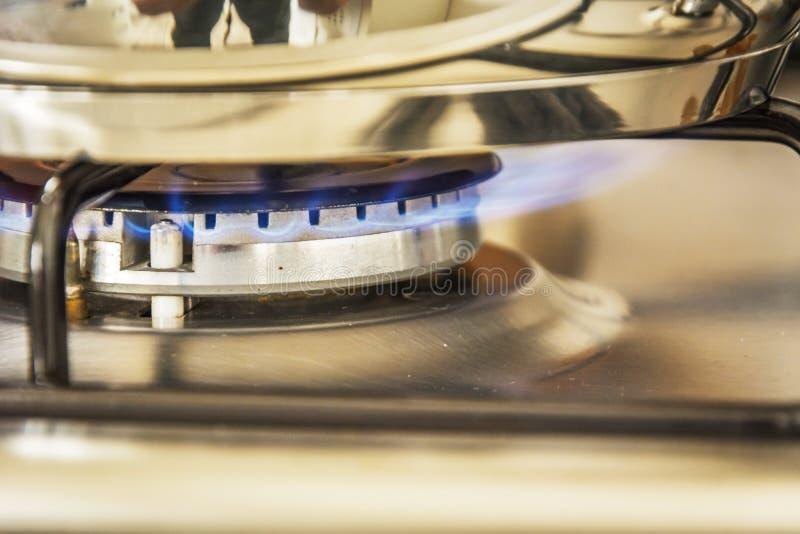 Ostrość błękitnego płomienia gaz na kuchenki gotowania garnku w kuchnia gazie s obraz royalty free