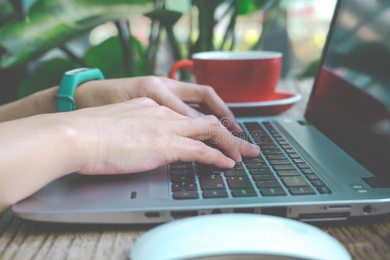 Ostrość na kobiety ręce używać laptop, gmeranie, sprawdzać, wyszukujący informację przy sklep z kawą, matte i hałasu filtr stosuj zdjęcie stock