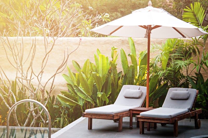 Ostrość punkt przy słońca łóżkiem i parasol wyrzucać na brzeg wokoło basenu obrazy royalty free