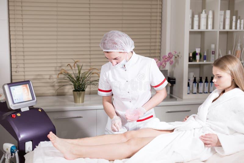 Ostrość w przedpolu ręka z przyrządem Doktorski cosmetologist robi procedurze młodej dziewczyny blondynki fotografia royalty free