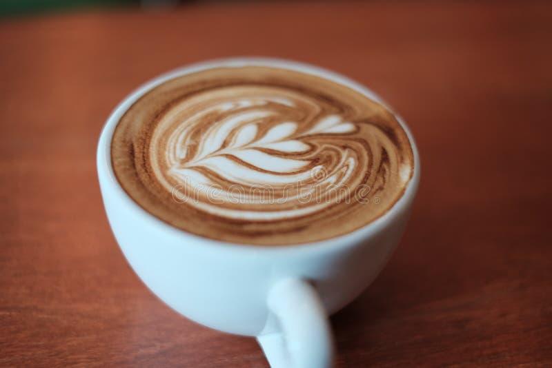 Ostrości gorący latte filiżanka na drewnie obraz royalty free