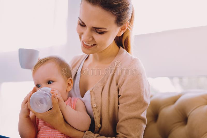 Ostrożna kobieta patrzeje jej dziecka podczas gdy trzymający butelkę woda fotografia stock