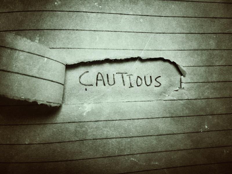 ostrożny angielski wyraz napisany ołówkiem na stronie cięcia papieru zdjęcie royalty free