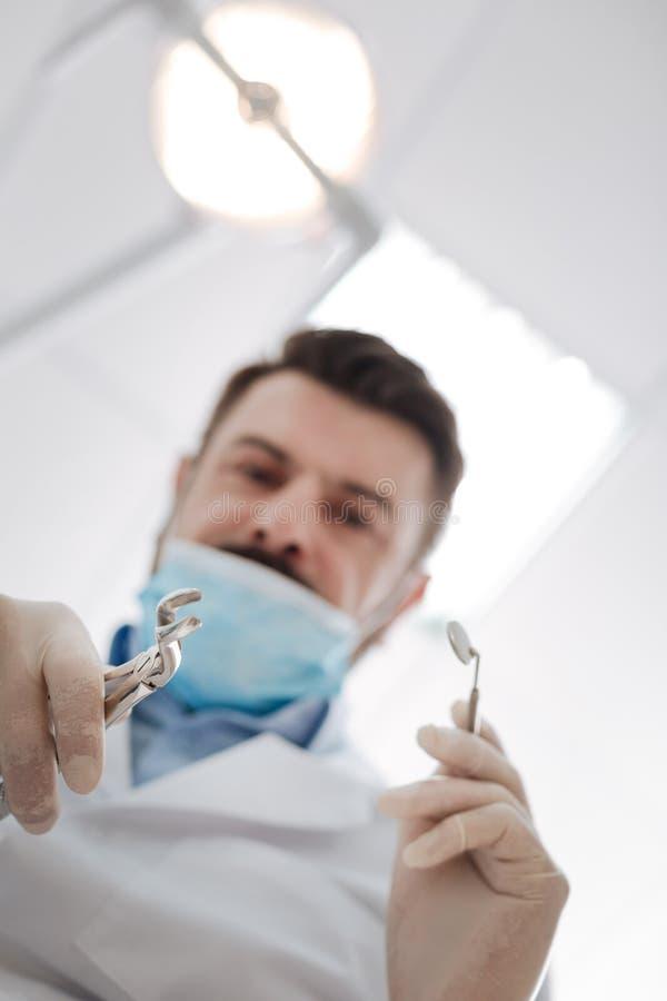 Ostrożny fachowy dentysta usuwa ząb obraz royalty free