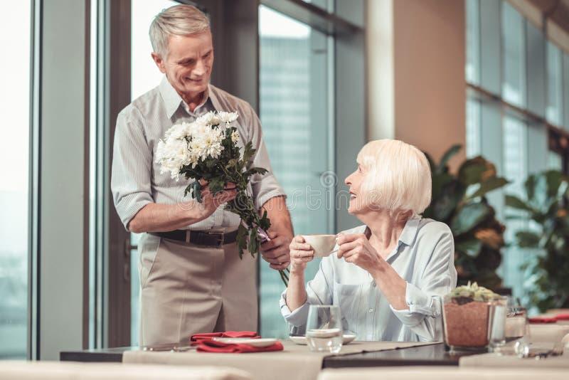 Ostrożny mężczyzna daje kwiaty przechodzić na emeryturę dama fotografia royalty free
