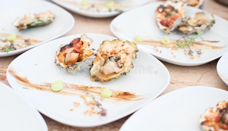 Ostron som lagas mat på en gallerlögn på en vit platta arkivbilder