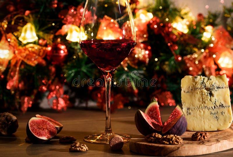 Ostroquefort med fikonträd, muttrar och en vinglas av rött vin på arkivbilder
