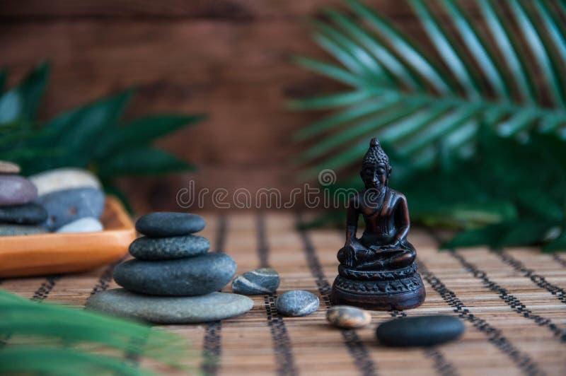 Ostrosłupy popielaci zen kamienie z zielonymi liśćmi i Buddha statuą Pojęcie harmonia, równowaga i medytacja, zdrój, masaż, relak zdjęcie royalty free