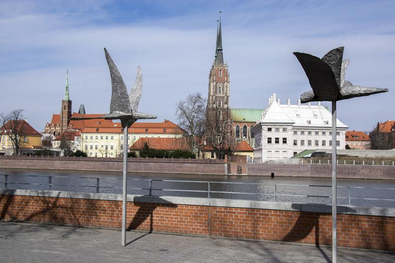Ostrow Tumski, Wroclaw / Poland - March 30, 2018: Odra river with Cathedral of St. John the Baptist bird sculpture stock image