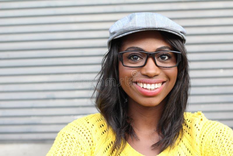 Ostry stylowy piękno Portret piękna młoda Afrykańska kobieta w szkłach i ostrym kapeluszowym ono uśmiecha się podczas gdy stojący obrazy stock