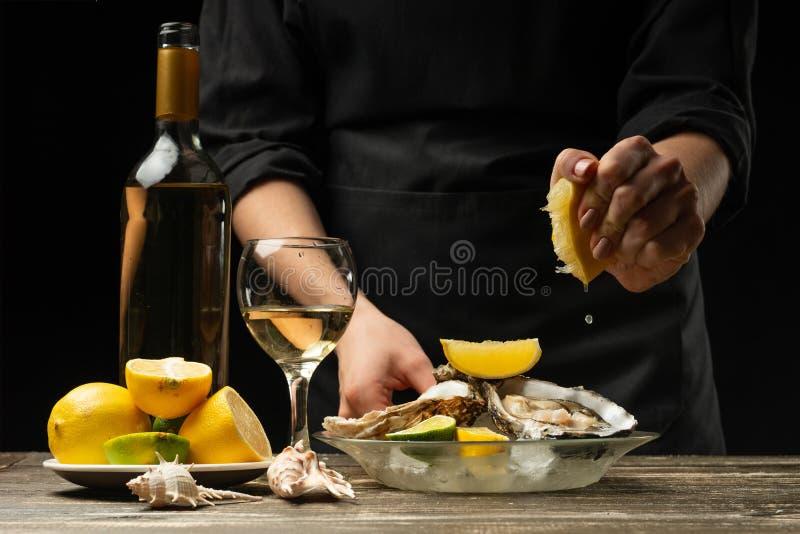 Ostrygi w talerzu z lodem i cytryną, w rękach szef kuchni i szkło bielu suchy Włoski wino, nalewa otwarte cytryn ostrygi fotografia royalty free
