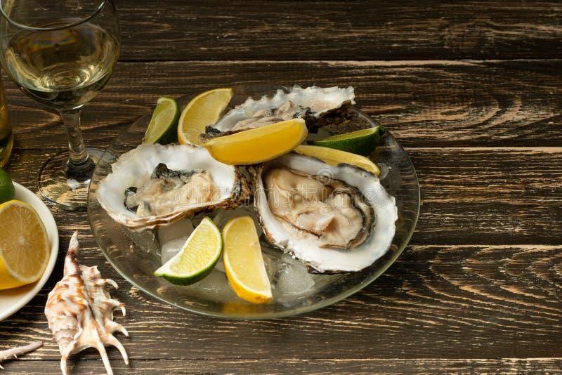 Ostrygi w talerzu z lodem i cytryną, z szkłem biały suchy wino na drewnianym tle Owoce morza, restauracja, wyśmienity smak obraz stock