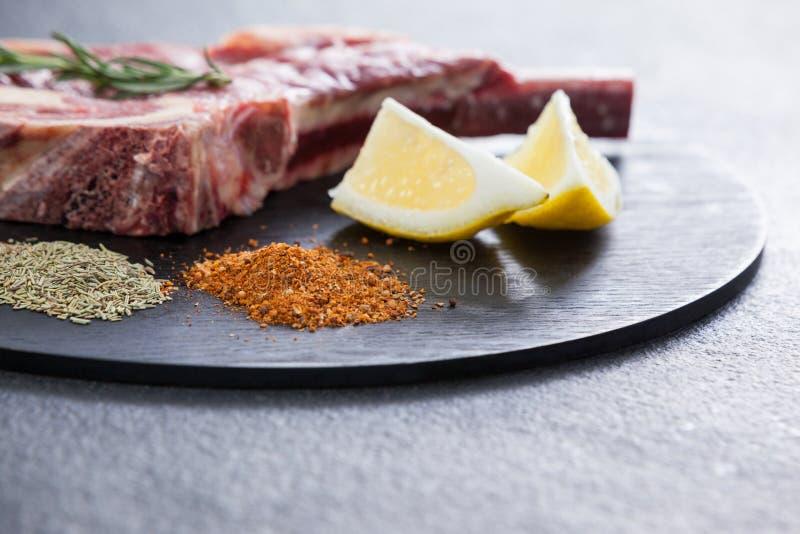 Ostrza kotlecik, pikantność i cytryna na czarnej round tacy, zdjęcie stock