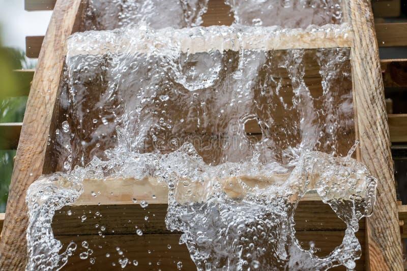 Ostrza młyński koło wirują pod strumieniem woda, fotografia stock