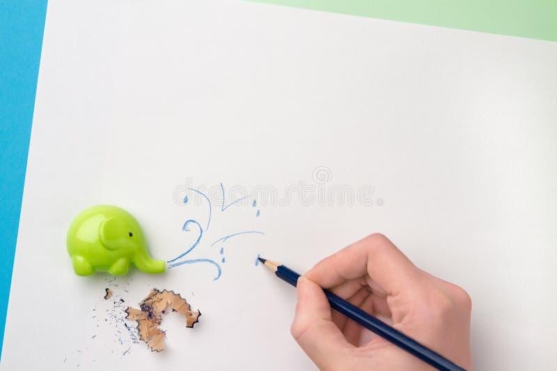 Ostrzarka, ręka z błękitnym ołówkiem, rysunek i ołówkowi segregowania Odgórny widok zdjęcia stock