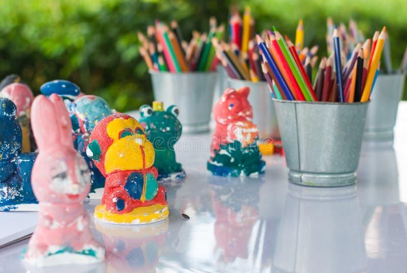 Ostrze i stępia kolorów ołówki stawia w wiadrze z tynk postacią gotową malującym w sztuka warsztacie dla dzieciaka obraz royalty free