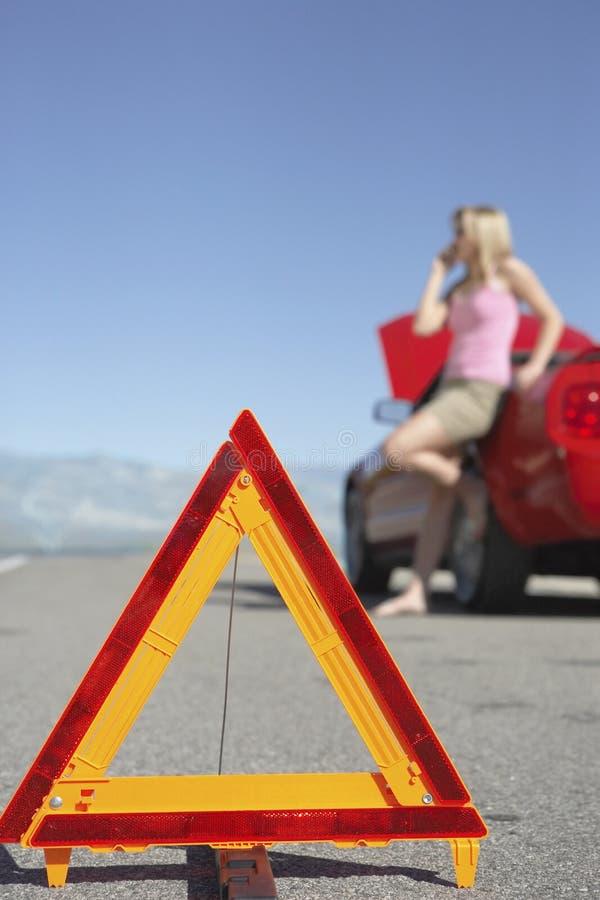 Ostrzegawczy trójbok Z kobietą Na wezwaniu samochodem Na drodze obraz stock