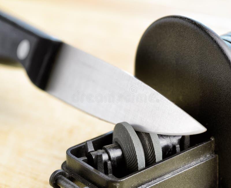 Ostrzenie nóż w kuchni obrazy stock