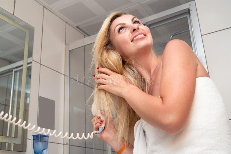ostrzyżenie Pięknej długiej z włosami kobiety suszarniczy włosy w łazience zdjęcia stock