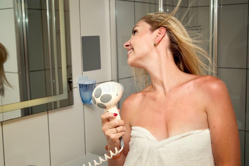 ostrzyżenie Pięknej długiej z włosami kobiety suszarniczy włosy w łazience obrazy stock